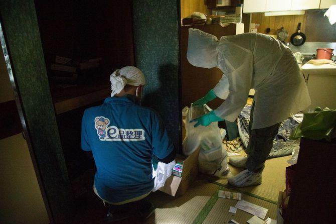 レインコートとゴム手袋を着用しゴミを分ける作業員