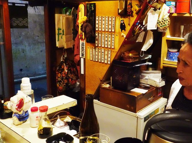 「串木乃」の店内とカウンターに立つママ