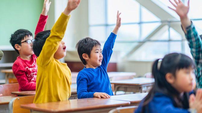 教室内で、挙手する子供たち