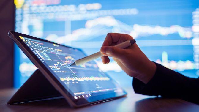 タブレット端末で株式市場データを探している女性
