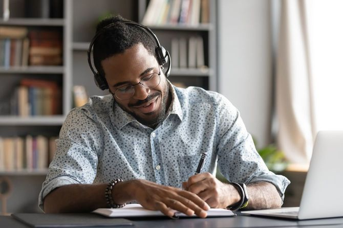 ヘッドセットを付けた笑顔の黒人男性が自宅でeラーニングの授業を受けている