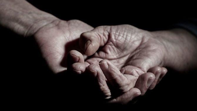 年配女性の手を握る男性の手