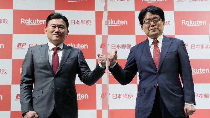 資本提携で合意し、ボード越しにこぶしを合わせる日本郵政の増田寛也社長(右)と楽天の三木谷浩史会長兼社長=2021年3月12日、東京・大手町