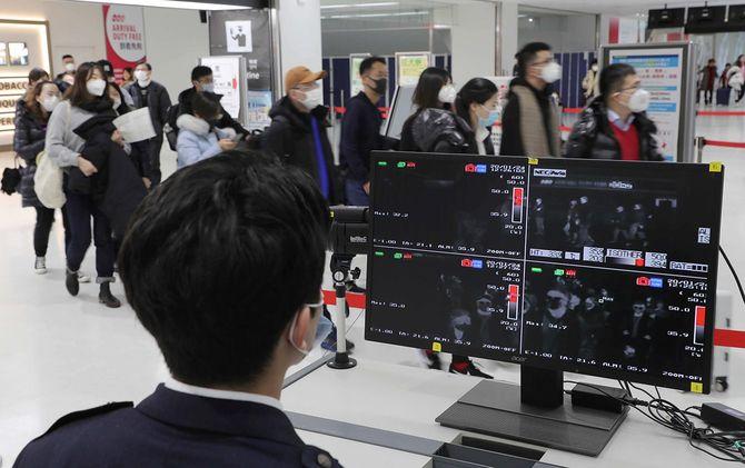 検疫所のサーモグラフィーで、到着した乗客の体温を確認する検疫官=2020年1月24日、千葉・成田空港