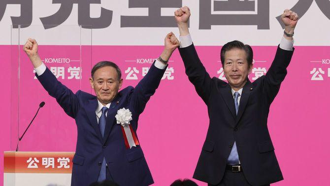 公明党の党大会で、壇上で山口那津男代表(右)と両手を上げる来賓として出席した菅義偉首相=2020年9月27日、東京都千代田区
