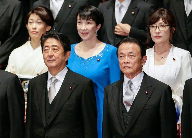 2016年8月3日、東京の首相官邸にて。安倍首相(当時)が行った内閣改造で新たに任命された稲田朋美防衛大臣(右上)、再任された高市早苗総務大臣(上中央)らと写真に納まる安倍晋三首相(左前)と麻生太郎財務大臣(右前)