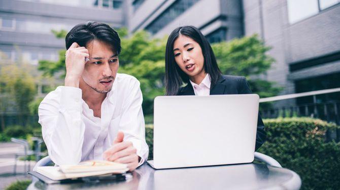 屋外でノートパソコンを開き、議論する2人のビジネスパーソン