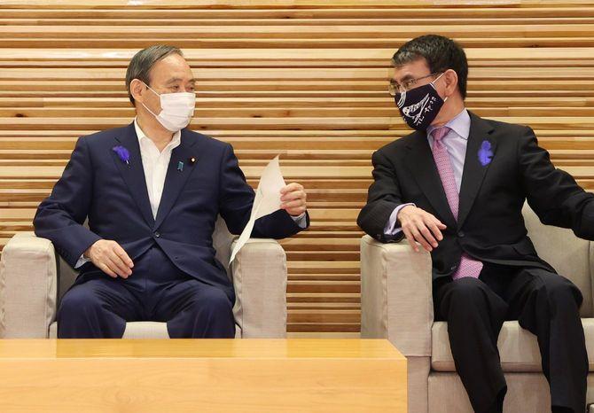 閣議前、河野太郎行政改革担当相(右)と話す菅義偉首相=2021年7月9日、首相官邸