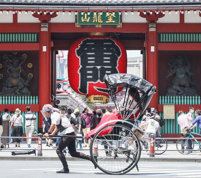 都道府県境をまたぐ移動が全面解禁後の初の週末を迎え、多くの観光客でにぎわう浅草・雷門の前を通過する人力車=2020年6月20日、東京都台東区