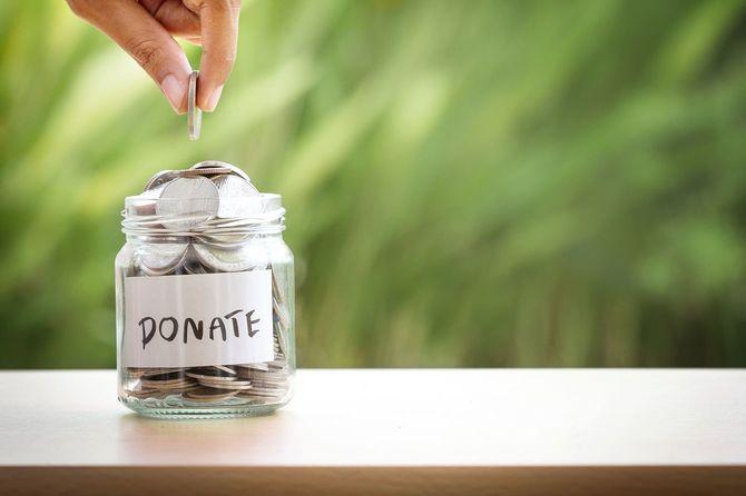 寄付のため瓶にお金を入れる