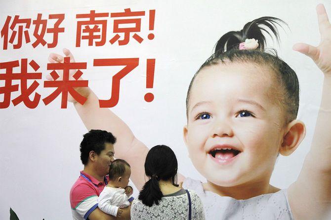 中国東部の江蘇省南京市で開催された展示会で、広告を見る家族=2014年9月13日