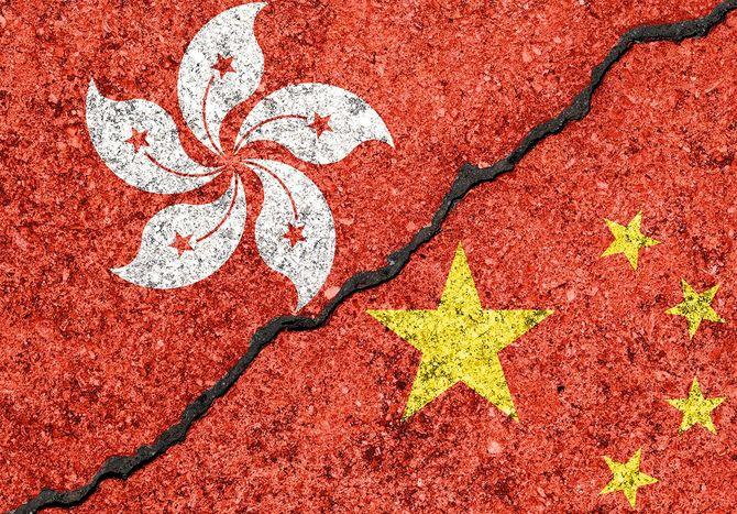ひび割れた壁の背景に描かれた香港と中国の旗/香港対中国紛争の概念
