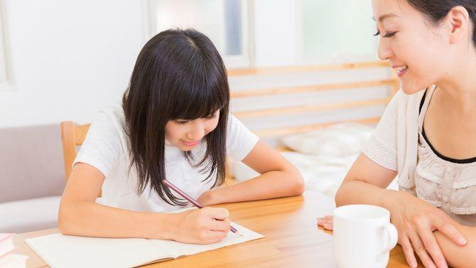 勉強する娘と付き添う母親