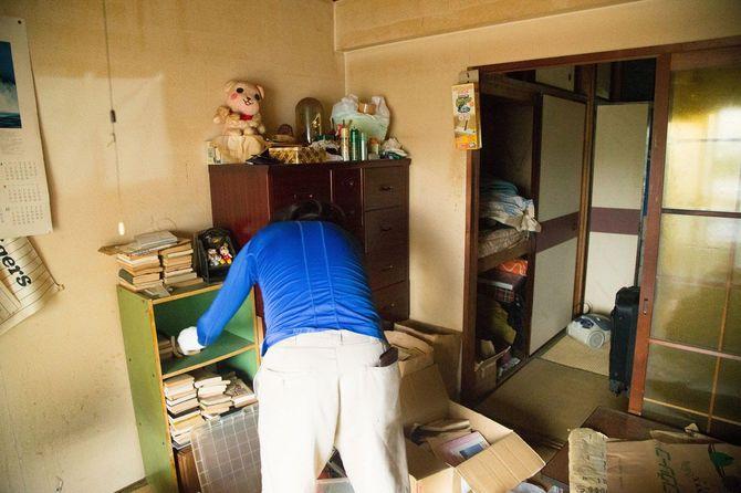段ボールや遺品が散乱する部屋で本棚を片付ける作業員