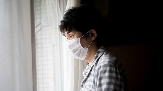 マスクを着用した男性が暗い部屋から外を見ている