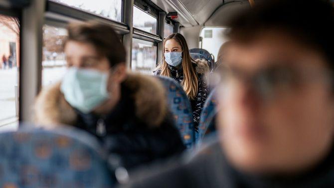 マスクを着用してバスに乗る若い女性