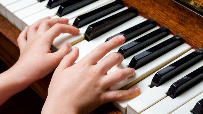 小さな女の子のピアノを弾く小さな手