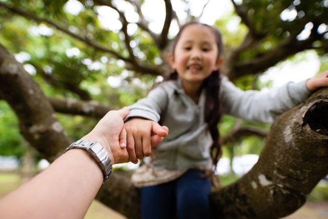 木登りをしている娘の手を握る父親