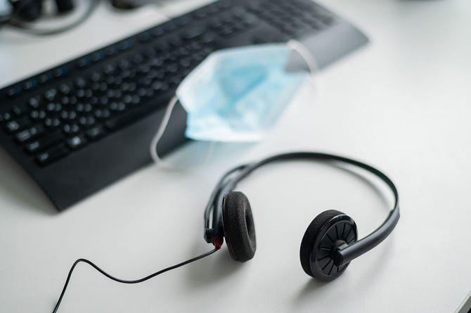オフィスのコールセンター、デスクトップのキーボードの近くにある医療用マスク