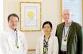 亀田隆明理事長とJCI認証取得に取り組んだジョン・C・ウォーカー氏と佐野元子さん。