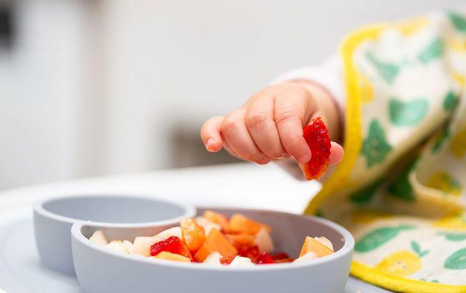 果物の一部と赤ちゃんの手