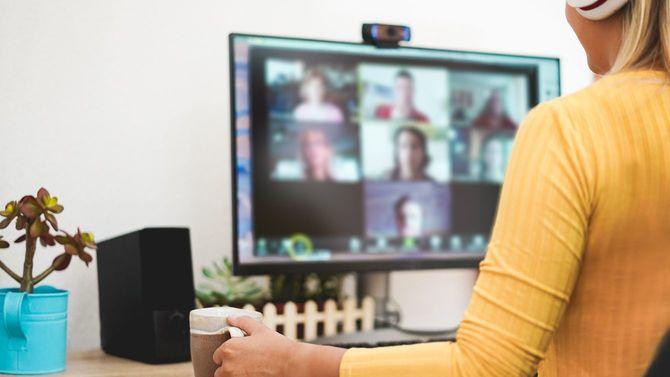 若い女性がチームとビデオ通話で意見交換をしている様子
