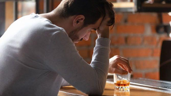 バーでウイスキーのグラスを手に頭を抱えている孤独な男性