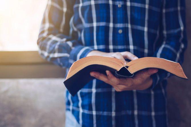 若いクリスチャン男性読書聖書