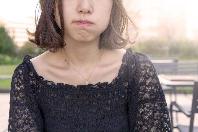 口をぎゅっと結ぶ若い女性