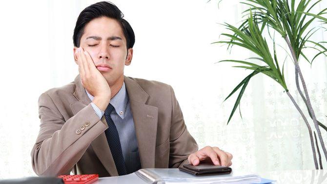 疲れ切ったビジネスパーソンの左手にはスマホ