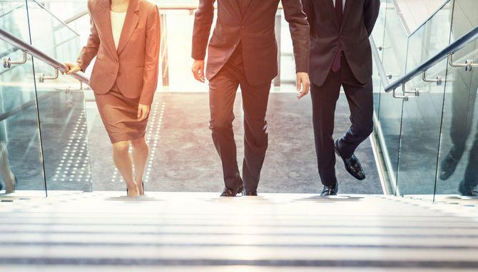 階段を上る3人のビジネスパーソン