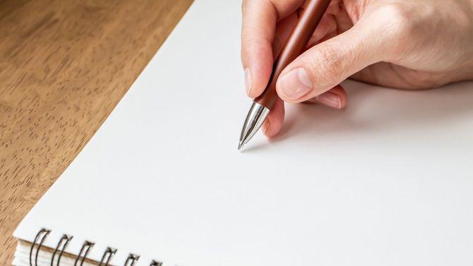 ノートにメモを取る女性の手元