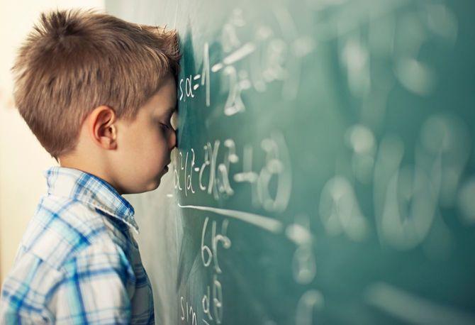 数式の書かれた黒板に参っている少年