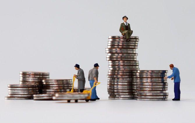 コインを運ぶミニチュアの人々とコインの上に座っているミニチュアの男