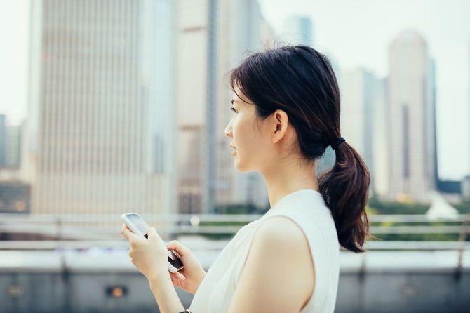 高層ビル群を背景にスマートフォンを持つ女性
