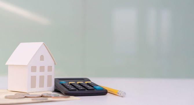 家の模型、電卓に鉛筆とコイン