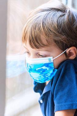 マスクを着用して悲しそうに窓の外を見つめる小さな男の子