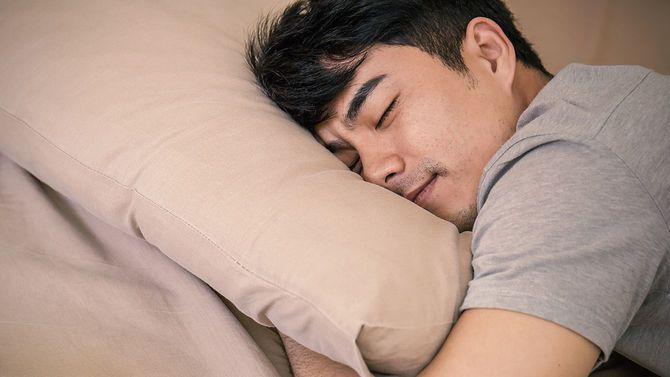 枕を抱えて眠る男性