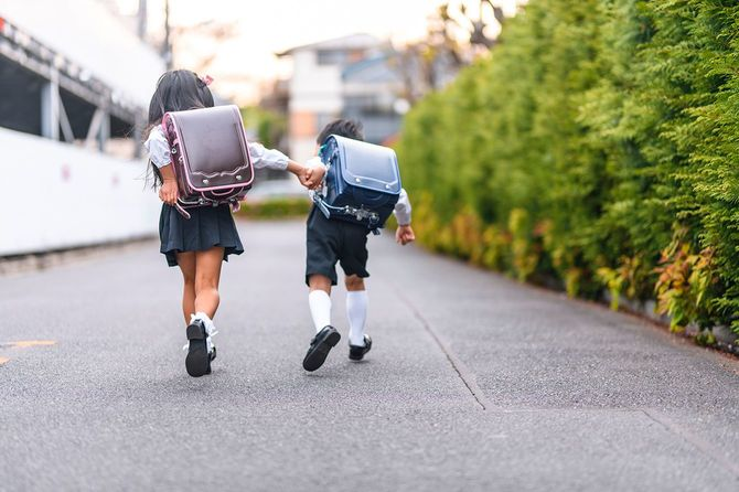 手をつないで走る日本の小学生