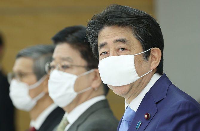 新型コロナウイルス感染症対策本部で、緊急事態宣言を5月31日まで延長することを表明する安倍晋三首相(右)
