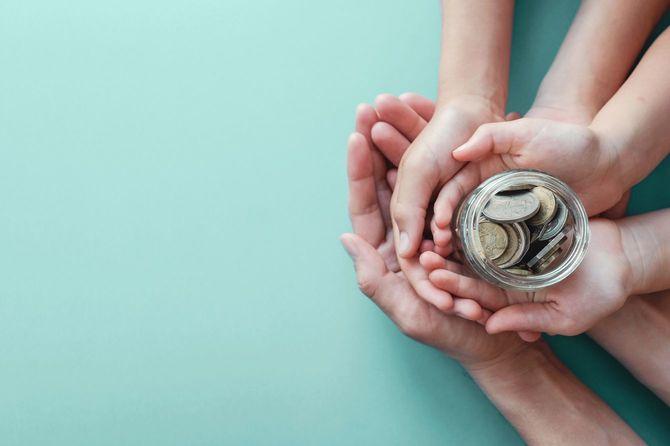 瓶に入れた硬貨を3代の手で包むように持っている