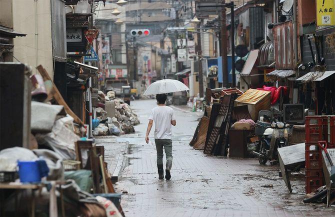小雨が降る中、災害ごみが積まれた道を進む男性