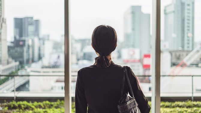 大都市で窓の外を見つめる女性