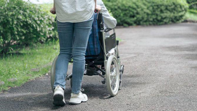 公園で車椅子を押して歩く若い女性