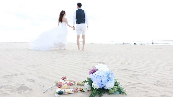 ビーチに置かれた花束とカップル
