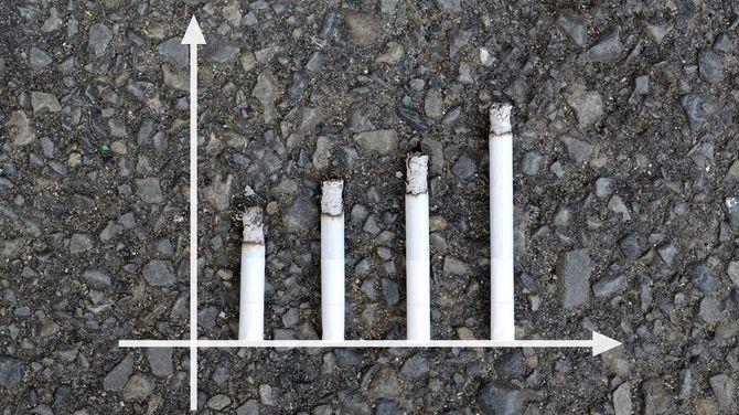 アスファルトの背景にタバコで構成されたグラフ