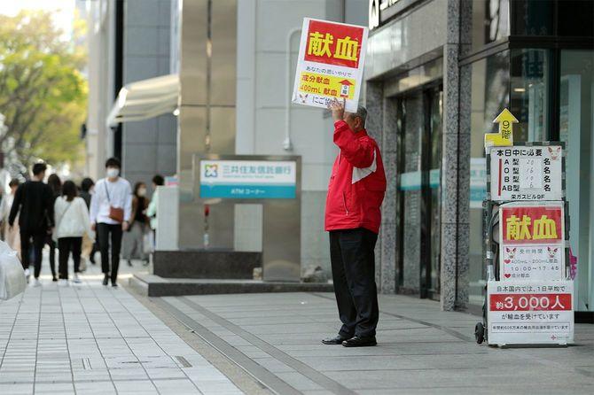 愛知県独自の「緊急事態宣言」が発令され、人通りの少なくなった中、献血を呼びかける男性=2020年4月11日、名古屋市中区