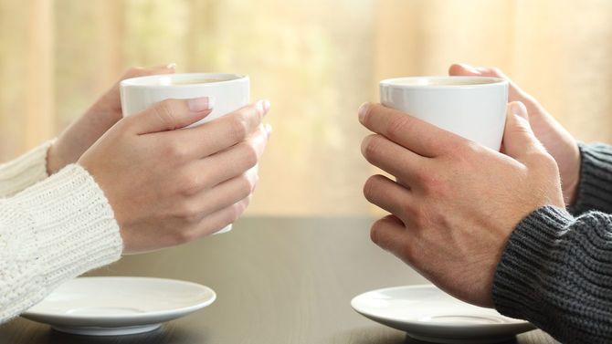 向かい合ってカップを手に持つカップルの手元