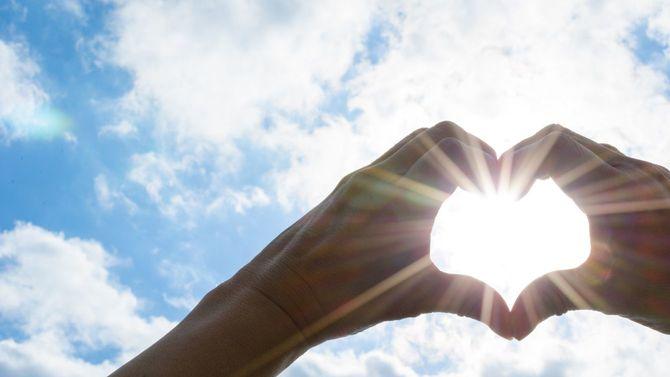 ハートの形をした手の向こうに太陽