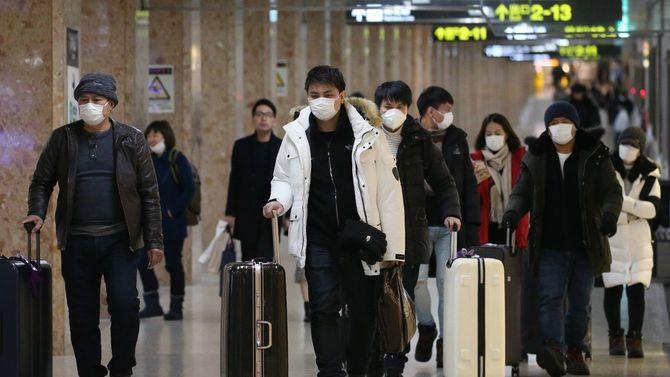 感染を防ぐためマスクをして地下道を歩く人たち=2月18日、北海道札幌市